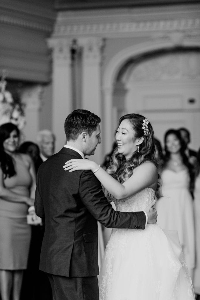 Black and white photo of the bride and groom during their first dance as husband and wife