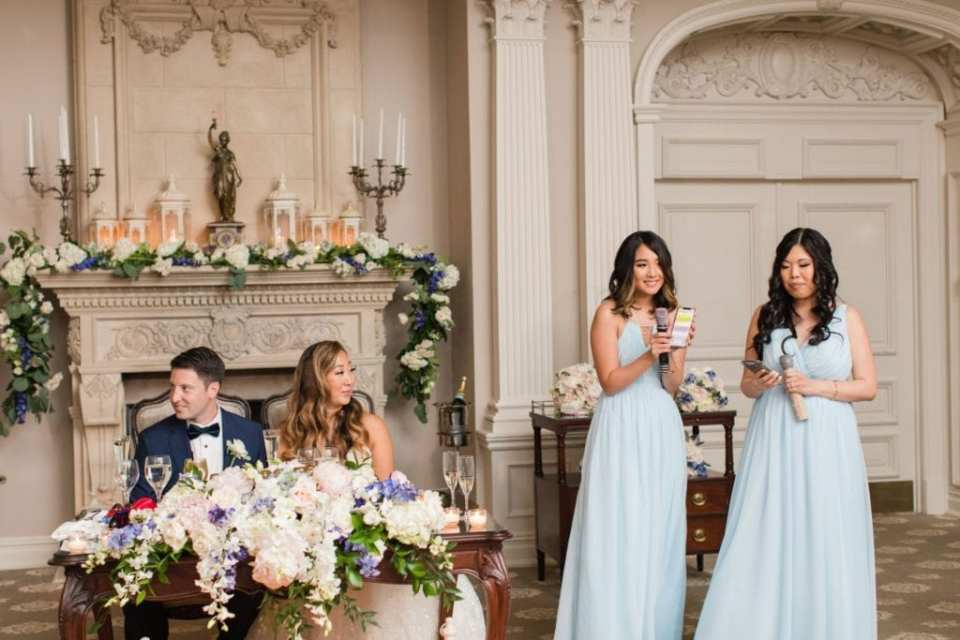 The maids of honor in pale blue gowns by Renzrags stand next to the couple seated at the sweetheart table as they make their speeches