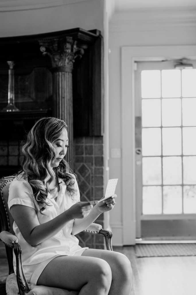 Black and white candid photo of the bride reading a letter from her groom