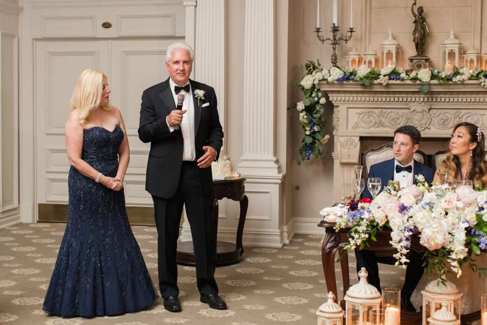 The groom's father and mother make a speech during the wedding reception
