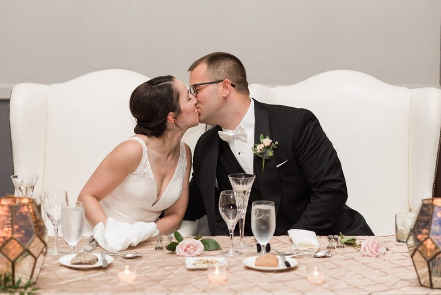 The bride and groom share a kiss at their sweetheart table during their wedding reception