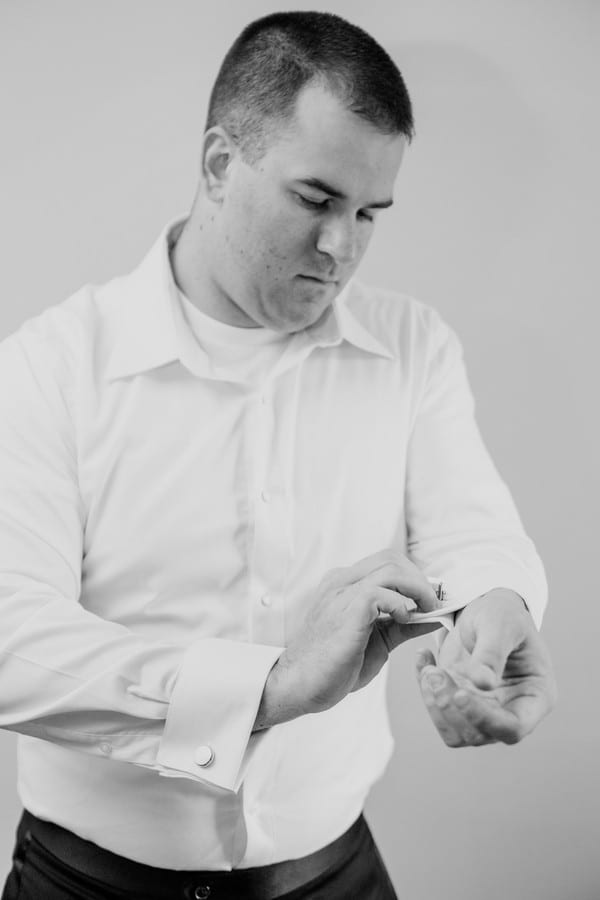 Black and white candid photo of the groom putting in his cuff links