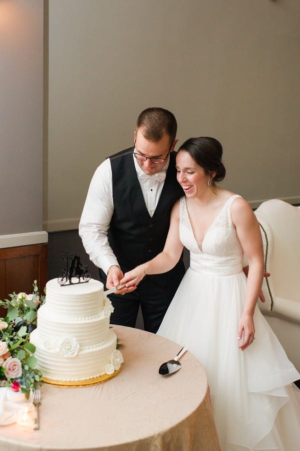 The bride and groom cut their three tier white buttercream patterned wedding cake by Cramer's Bakery