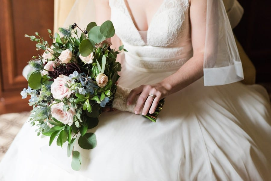 Focus on the brides Mikella Bridal gown, her engagement ring holding her bridal bouquet during her Princeton Marriott at Forrestal Wedding Photos