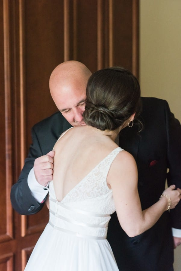 The bride shares a hug with her father after he saw her for the first time in her gown