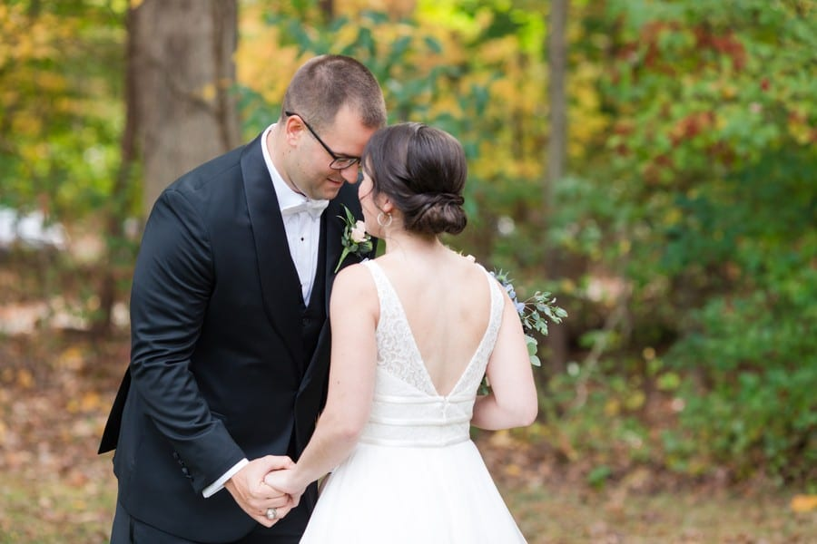 The groom sees his bride for the first time during their first look, foreheads together, hands holding