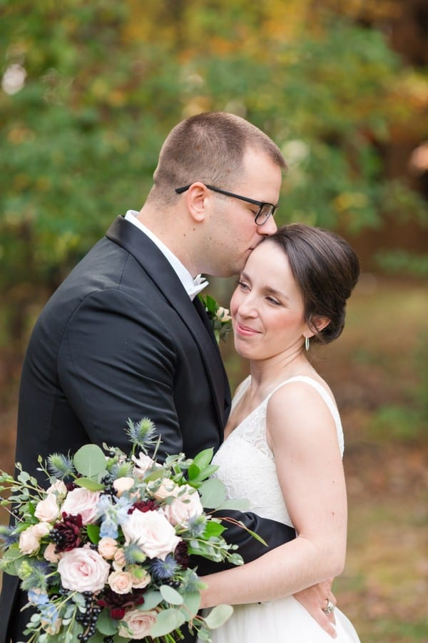 Close up of the groom kissing his bride on her temple, her bouquet of greens, blush and burgundy florals with bits of blue in view