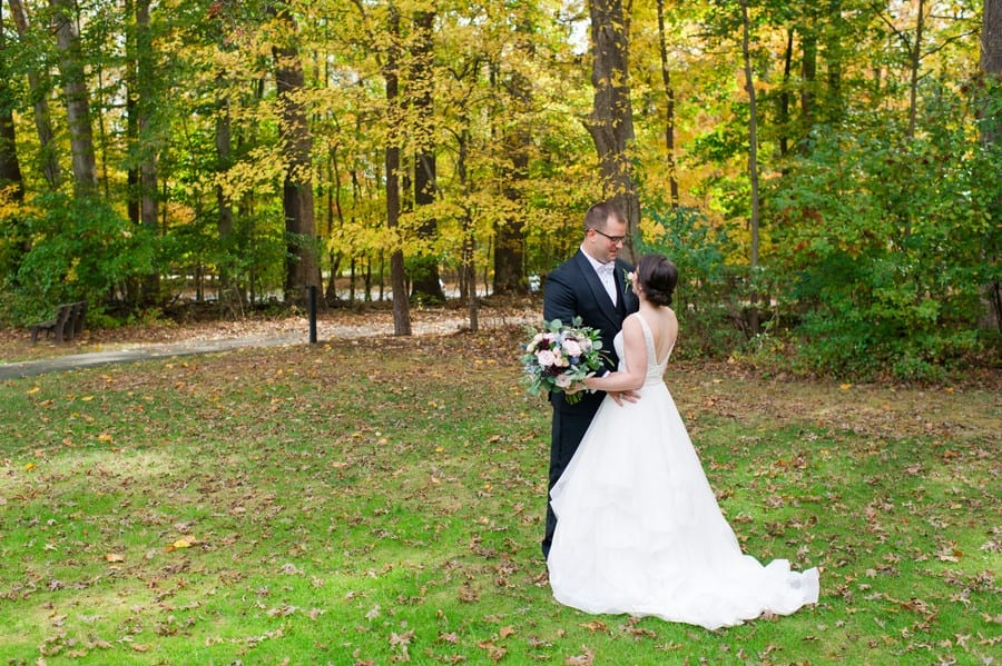 The bride and groom enjoying a tender moment in one anothers arms during portraits outside