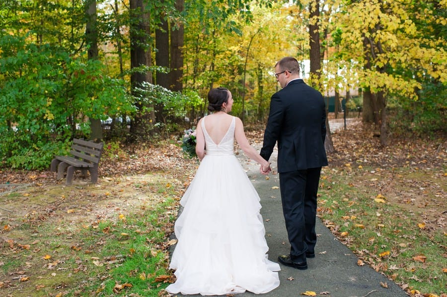 The bride and groom hold hands while walking away from the camera amongst fall foliage in Princeton