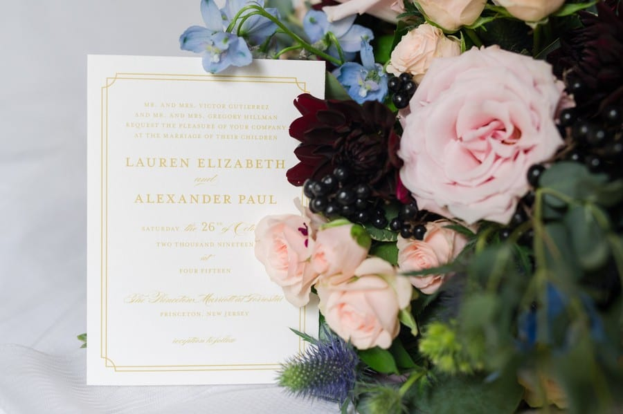 Wedding details: the wedding invitation in gold and cream displayed with the bridal bouquet of blush, burgundy and blue florals