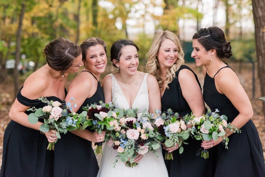 The bride in a gown by Mikella Bridal in a fun photo with her bridal party in black gowns by Bill Levkoff, florals by Petal Pushers