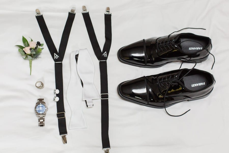 The grooms details of shoes, suspenders, watch, bowtie on display
