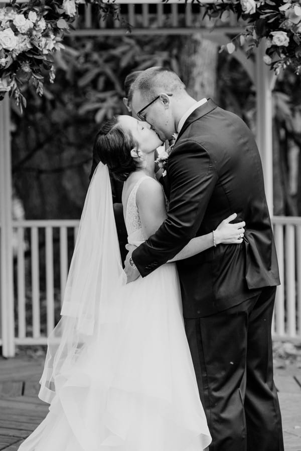 Black and white photo of the bride and groom having their first kiss as husband and wife