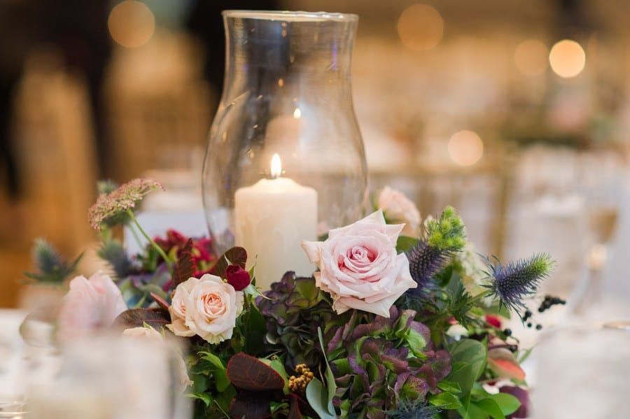 Wedding details: low mixed florals with a candle hurricane holder in the middle by Petal Pushers at the Princeton Marriott at Forrestal wedding