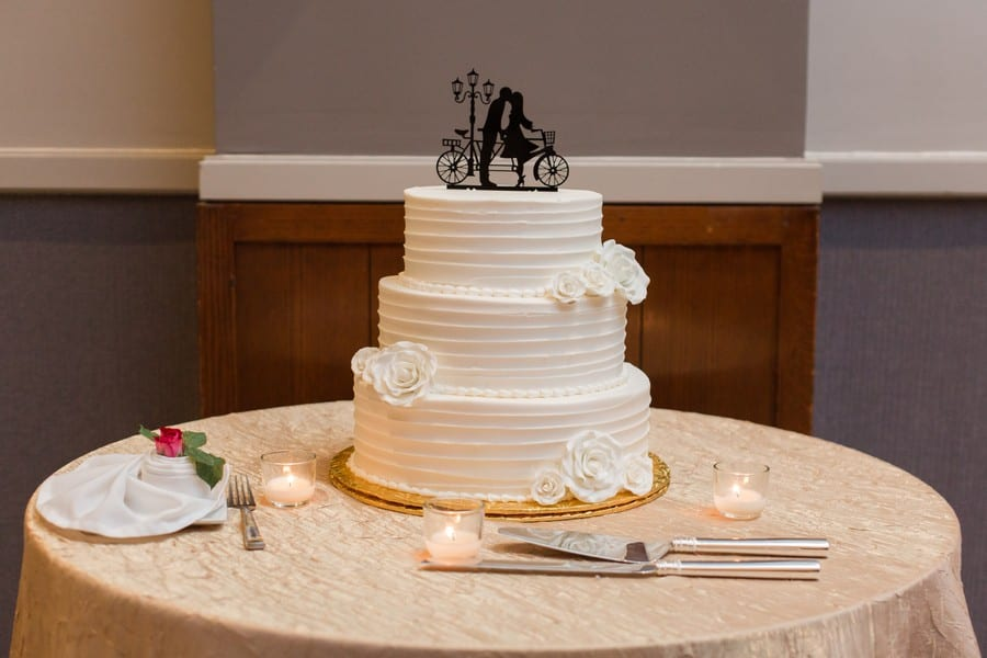 Three tiered patterened white wedding cake by Cramers Bakery with custom black kissing bicyclist wedding topper