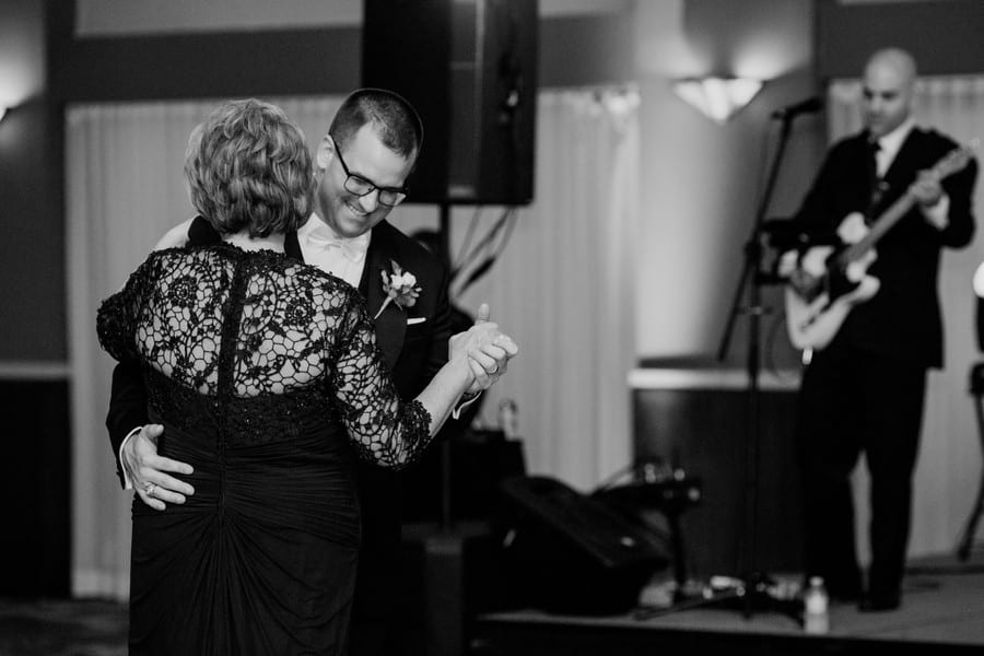Black and white photo of the groom dancing with his mother