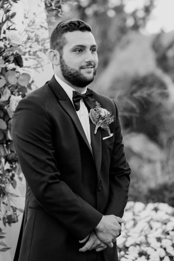 Black and white photo of the groom smiling as he sees his bride appear at the end of the aisle