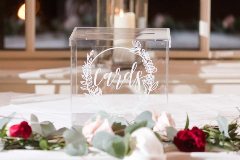 Acrylic card box on display with florals around it
