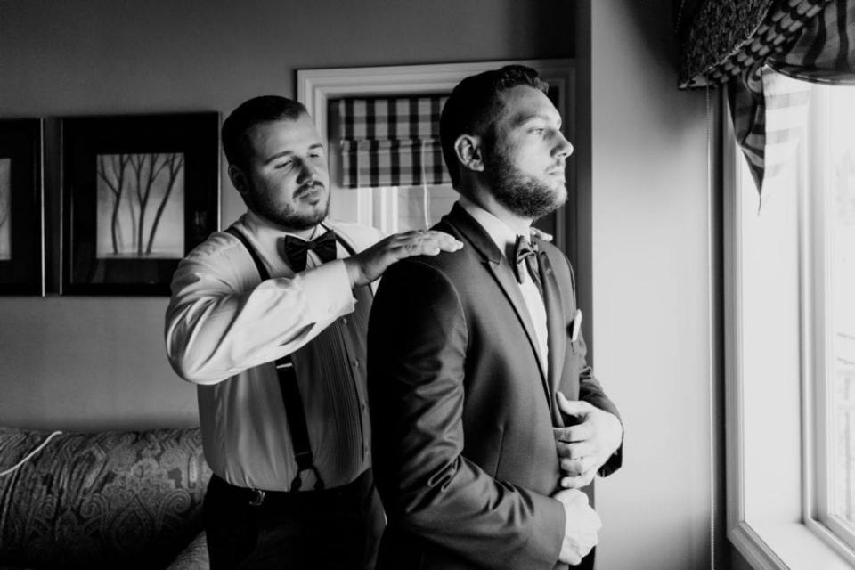 Black and white photo of the groom being assisted with his tuxedo by a groomsman