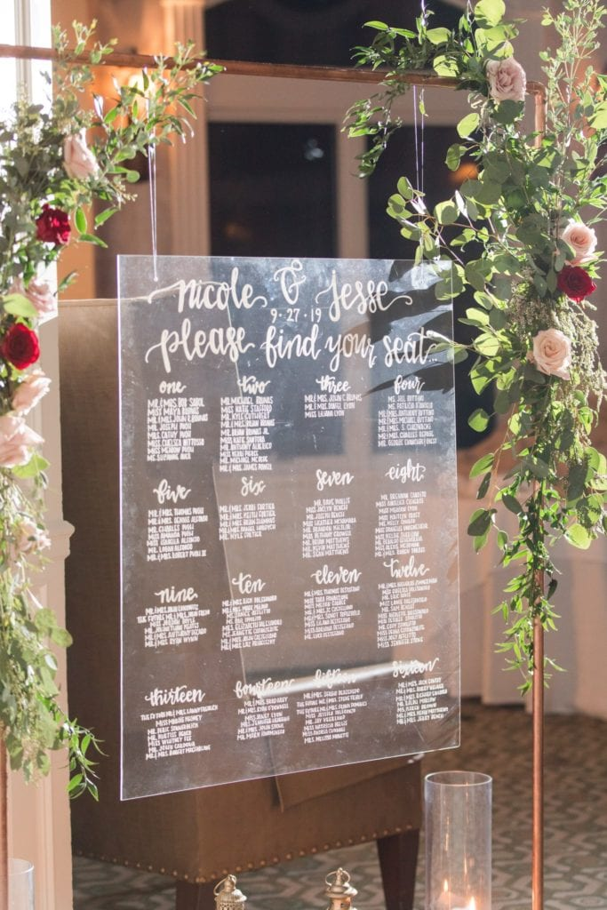Clear acrylic table arrangement signage hanging from copper piping decorated with greenery and florals in shades of blush and red by Added Touch Florist
