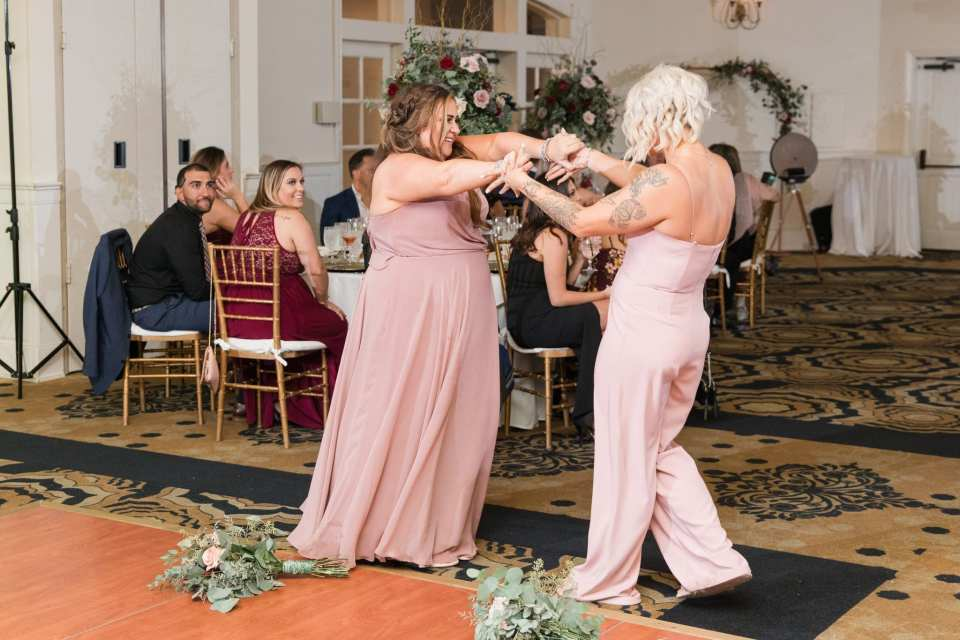 Members of the wedding party, in pink attire by Bella Bridesmaids, make a fun entrance into the wedding reception