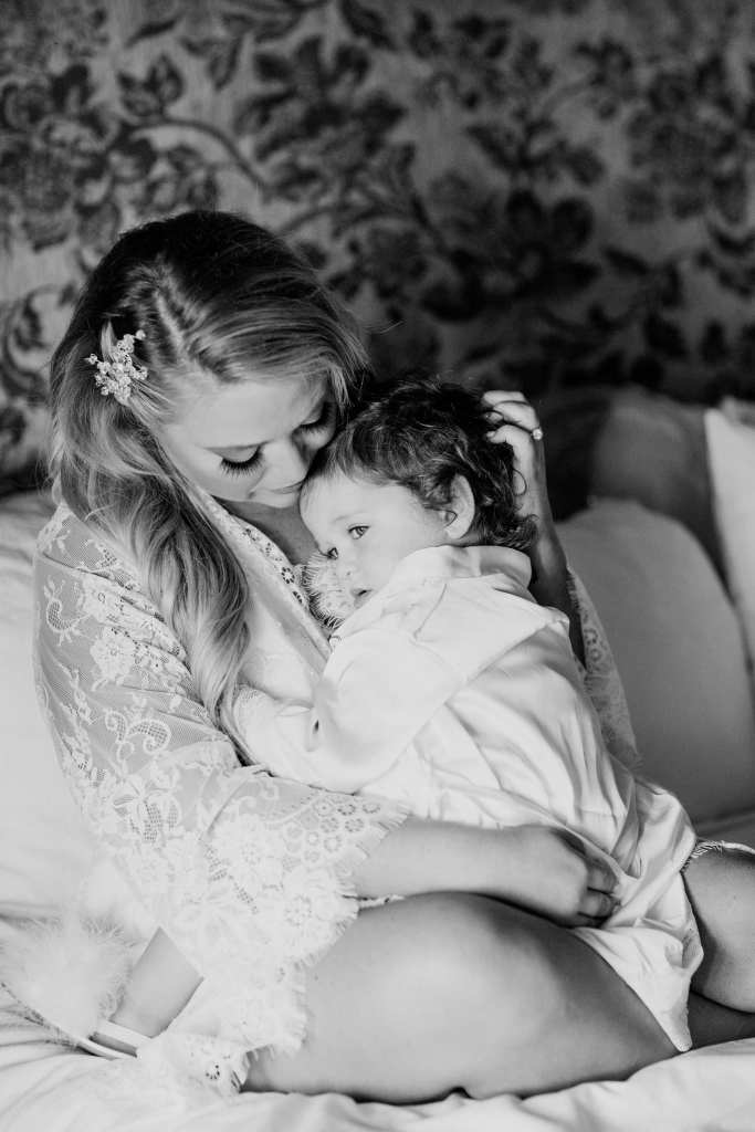 Black and white candid photo of the bride in a lace robe, sitting on the bed in the bridal suite, cuddling her toddler daughter