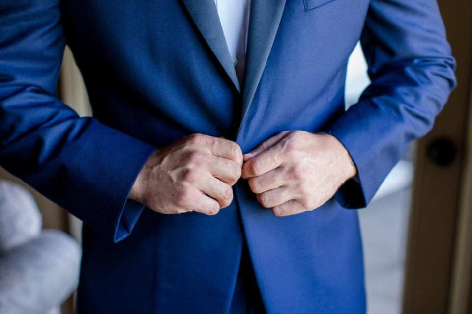 Close up of the grooms hands buttoning his navy blue Chazmatazz tuxedo