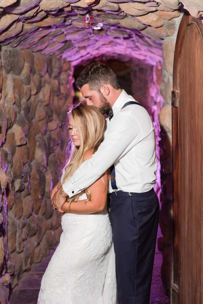 Bride with groom's arms wrapped around her from behind, share an intimate moment in the wine cellar at the Grand Cascades Lodge at Crystal Springs Resort