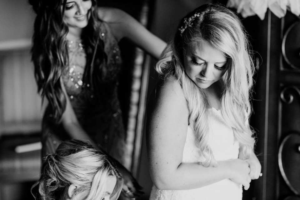 Black and white candid photo of the bride being helped into her Pronovias gown by her maids of honor. Hair by Colorbar the Salon