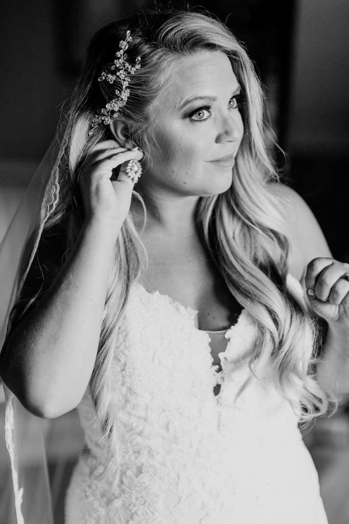 Black and white photo of the bride putting in her earrings after putting on her Pronovias wedding gown