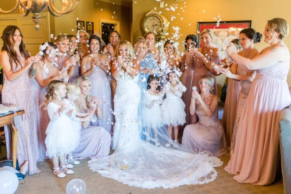 The bride and her bridal party pop confetti poppers inside the bridal suite after getting ready for the wedding