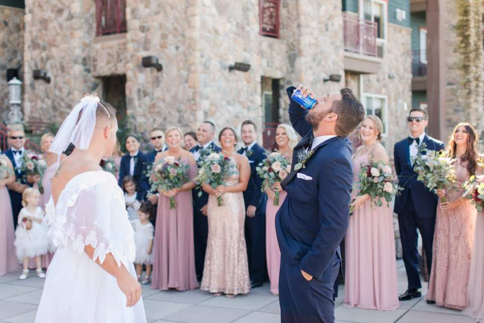 The groom takes a sip of a beer during a faux first look, where a groomsman dressed up in a white wedding gown as a joke