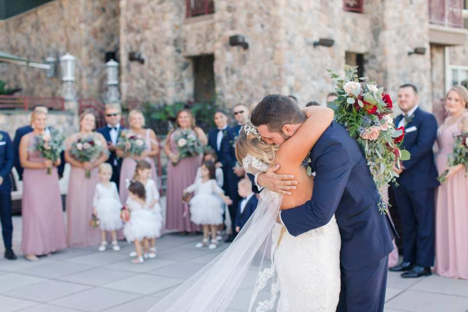 The bride and groom embrace while surrounded by their wedding party