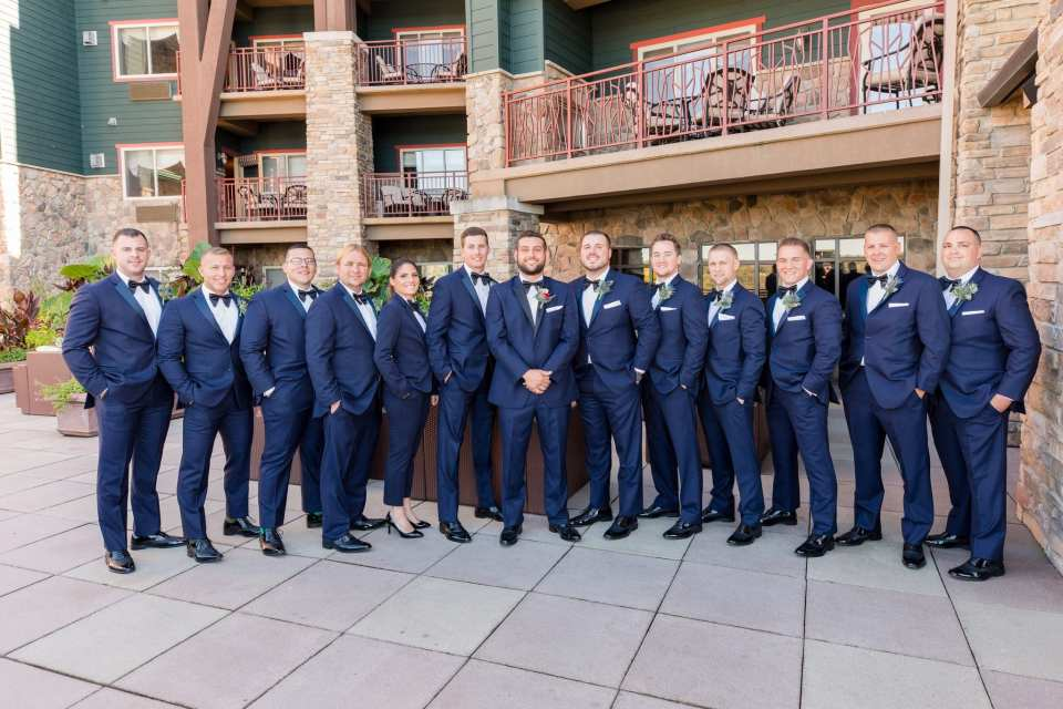 Formal portrait of the groom and his groomspeople in navy blue and black tuxedos by Chazmatazz