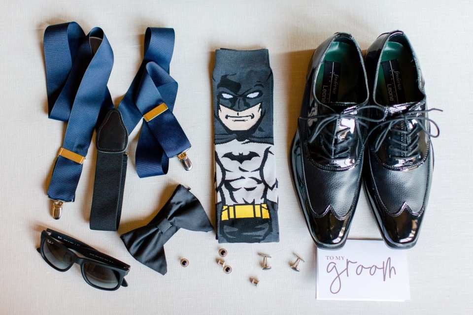 Close up of groom details: suspenders, bowtie, sunglasses, cufflinks, Batman socks, black shoes, and a card from his bride