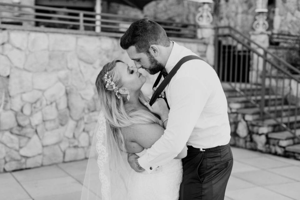 Black and white photo of the bride and groom nose to nose, she pulling him in closer by his suspenders