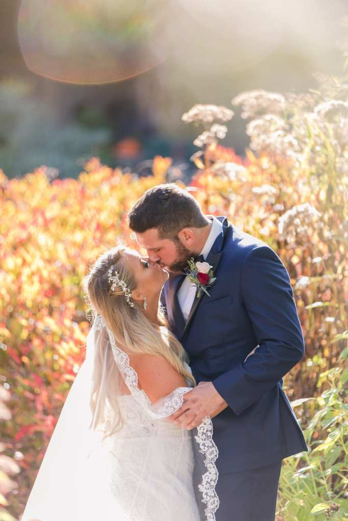 Portrait of the couple kissing against fall foliage in the background