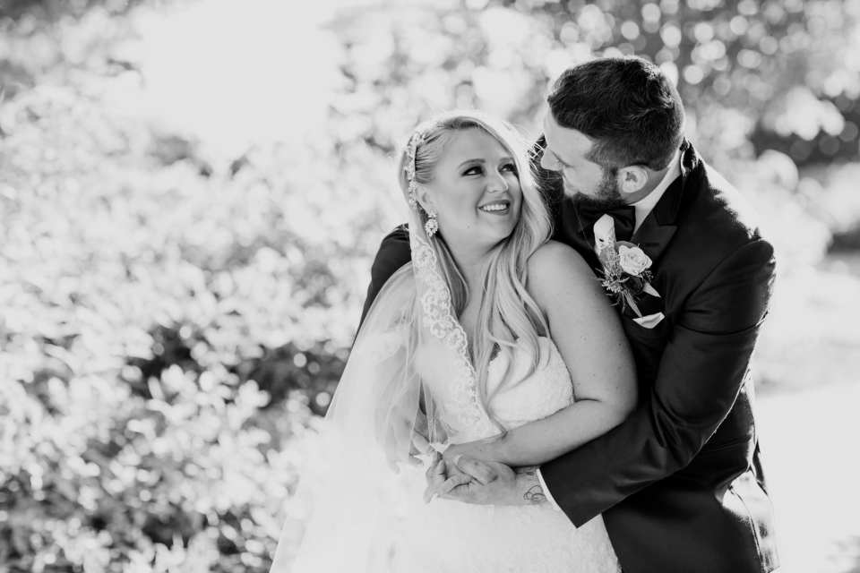 Black and white photo of the groom wrapping his arms around his bride, she looking up at him, he looking down at her