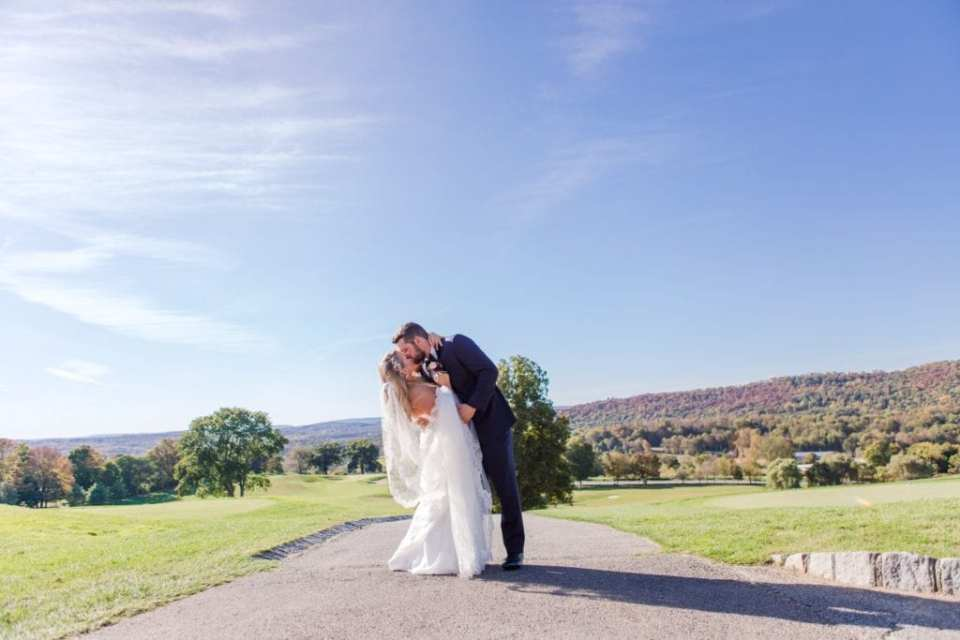 Wide angle photo of groom dipping his bride for a kiss, the fall colored trees on the mountains of Northern New Jersey in the background