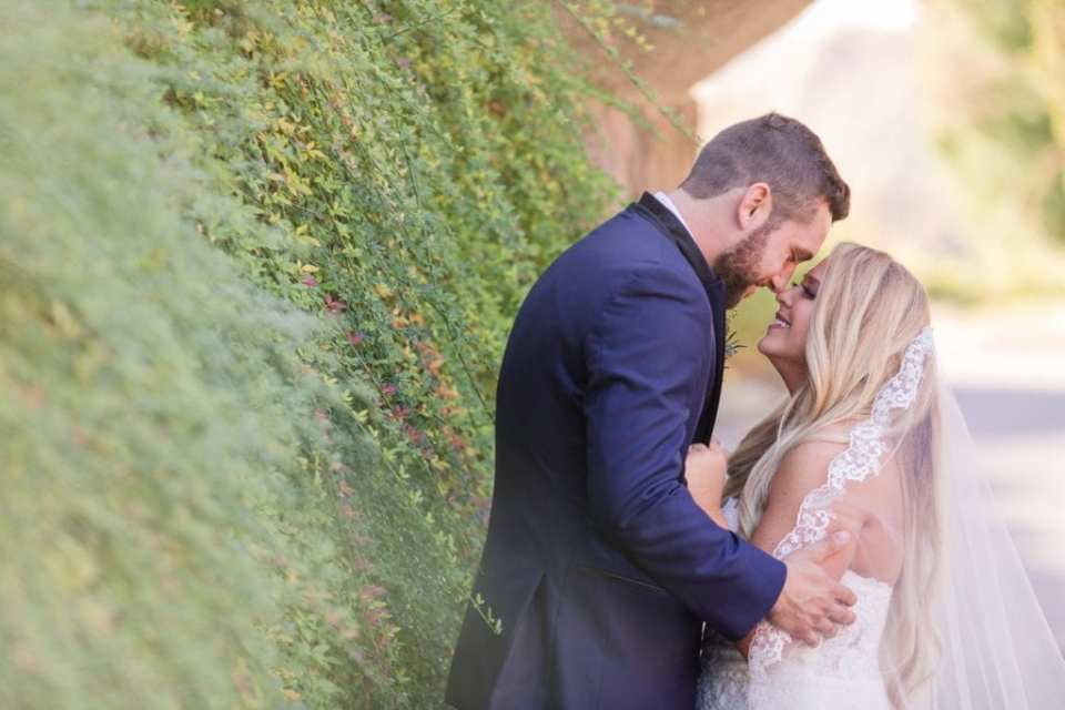 Side shot of bride and groom, nose to nose, against a wall of greenery