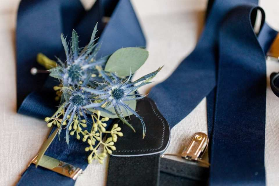 Close up of the grooms details: suspenders and boutonniere