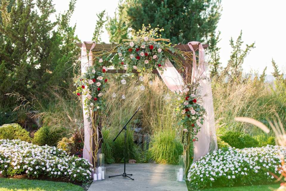 Close up of the outdoor ceremony space under a dark wood trellis decorated with pink fabric, greenery, blush and red roses and clear hanging candleholders by Added Touch Florist at the Grand Cascades Lodge at Crystal Springs Resort