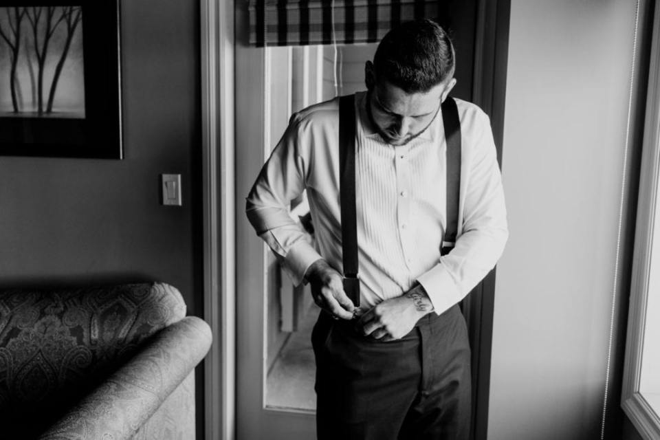 Black and white photo of the groom putting on his suspenders