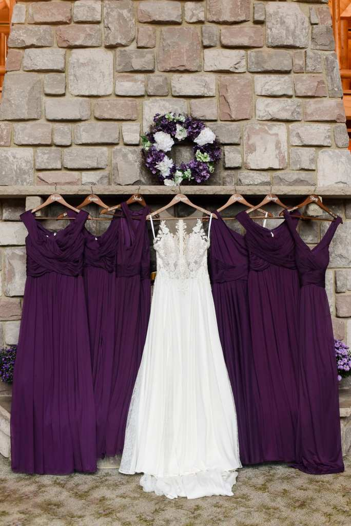 The brides gown by Allure Bridal on display with the plum bridesmaids gowns by David's Bridal on a stone fireplace mantle in these Blue Mountain Resort wedding photos