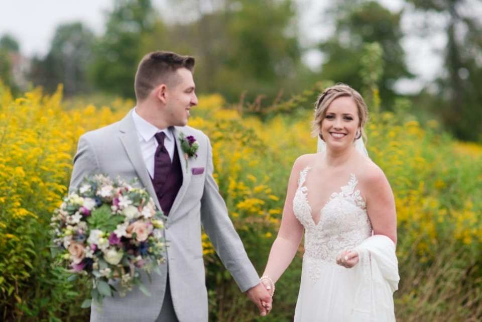 The groom in a light grey suit with purple tie leads his bride outdoors in front of a field of yellow wildflowers in these Blue Mountain Resort Wedding photos
