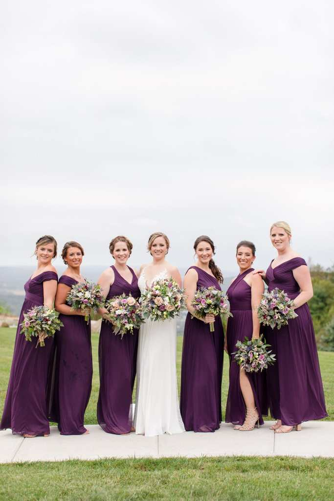The bride in her Allure bridal gown and her bridemaids in a purple off the shoulder gown by David's Bridal holding a bouquet of wildflowers by Ross Plants & Flowers