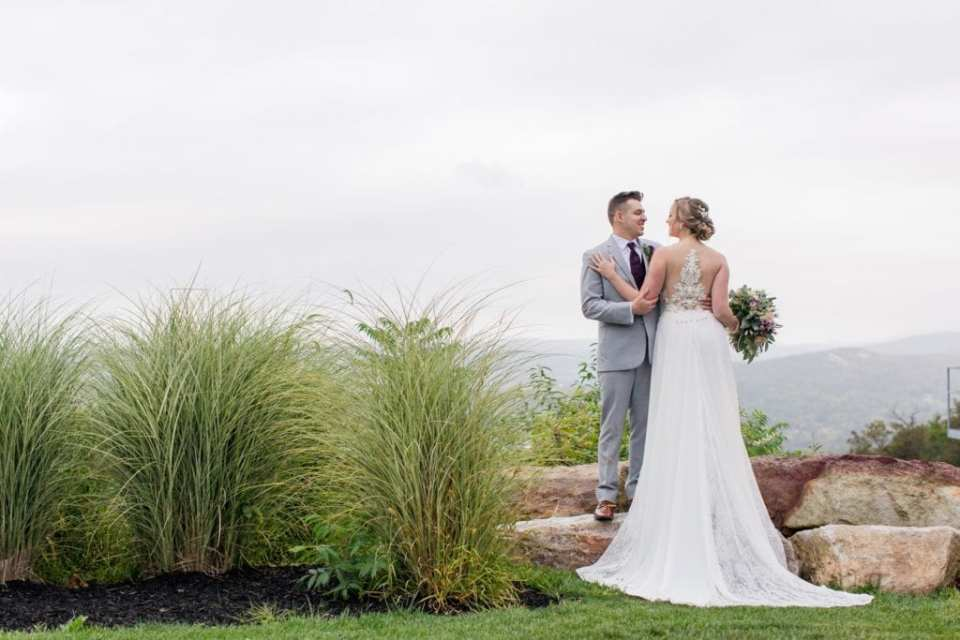 Full length portrait of the bride and groom, her with her back to the camera showcasing the back of her Allure bridal gown detail, he facing the camera outdoors for their Blue Mountain Resort wedding photos