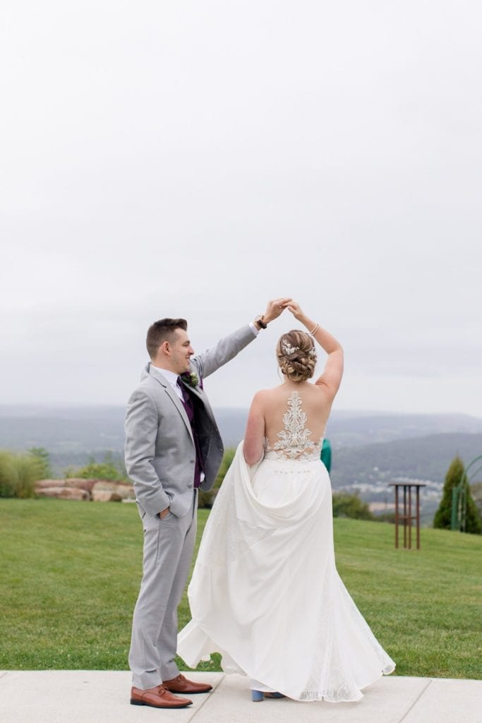 The groom twirls his bride, showing off the back lace applique of her Allure bridal gown outside, with the mountains of North Jersey in the background in these Blue Mountain Resort Wedding photos