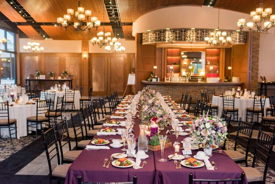 Wide angle photo of a long rectangular table with short wildflower and green floral arrangements in small glass vases, surrounded by other lower wildflower arrangements by Ross Plants and Flowers in these Blue Mountain Resort Wedding photos