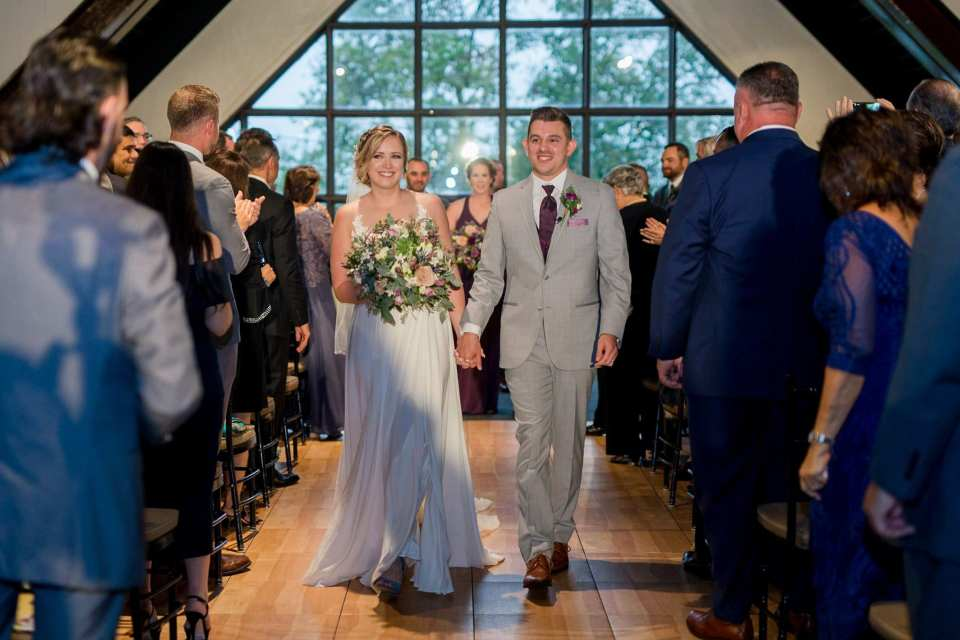 The bride and groom make their way down the aisle as husband and wife